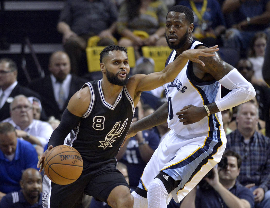 San Antonio Spurs guard Patty Mills (8) controls the ball against Memphis Grizzlies forward JaMychal Green during the first half of Game 3 in an NBA basketball first-round playoff series Thursday, ...