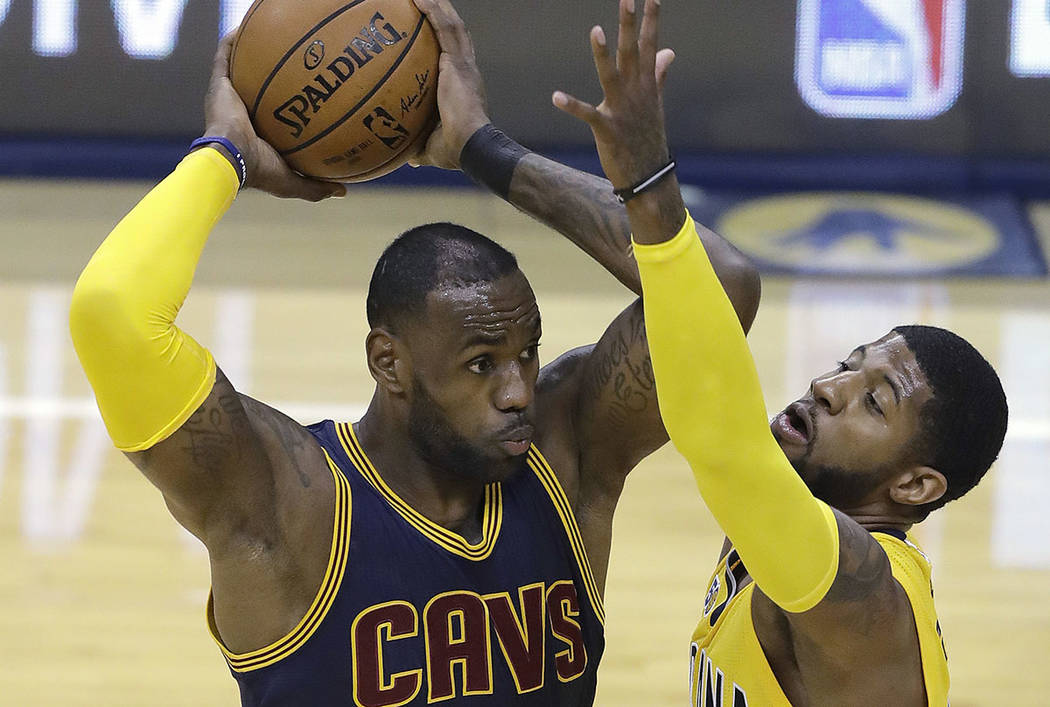 Cleveland Cavaliers' LeBron James keeps the ball from Indiana Pacers' Paul George during the first half in Game 3 of a first-round NBA basketball playoff series, Thursday, April 20, 2017, in India ...