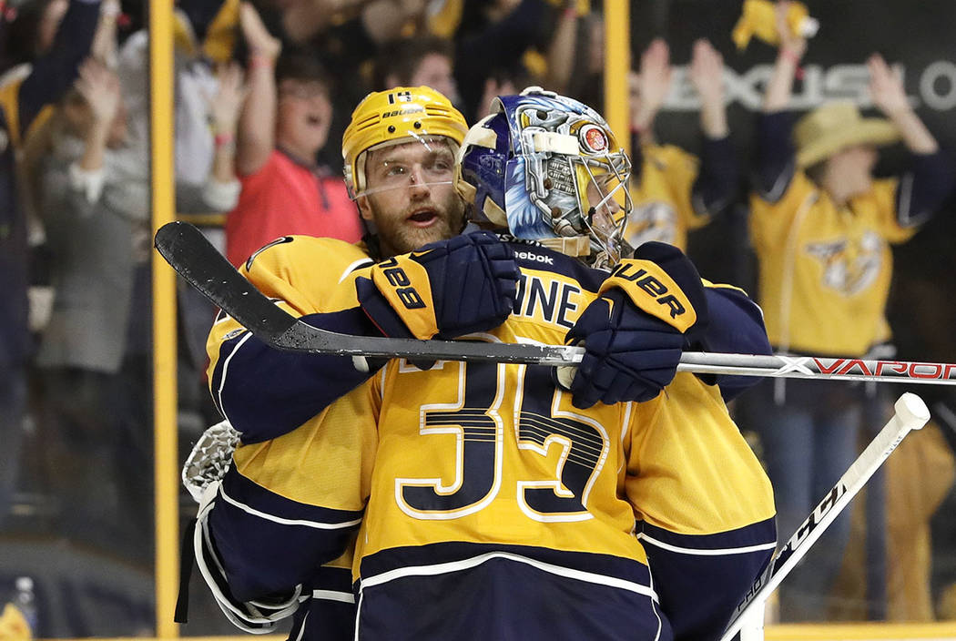 Nashville Predators defenseman Mattias Ekholm, left, of Sweden, hugs goalie Pekka Rinne (35), of Finland, in the final seconds of Game 4 of the team's first-round NHL hockey playoff series against ...