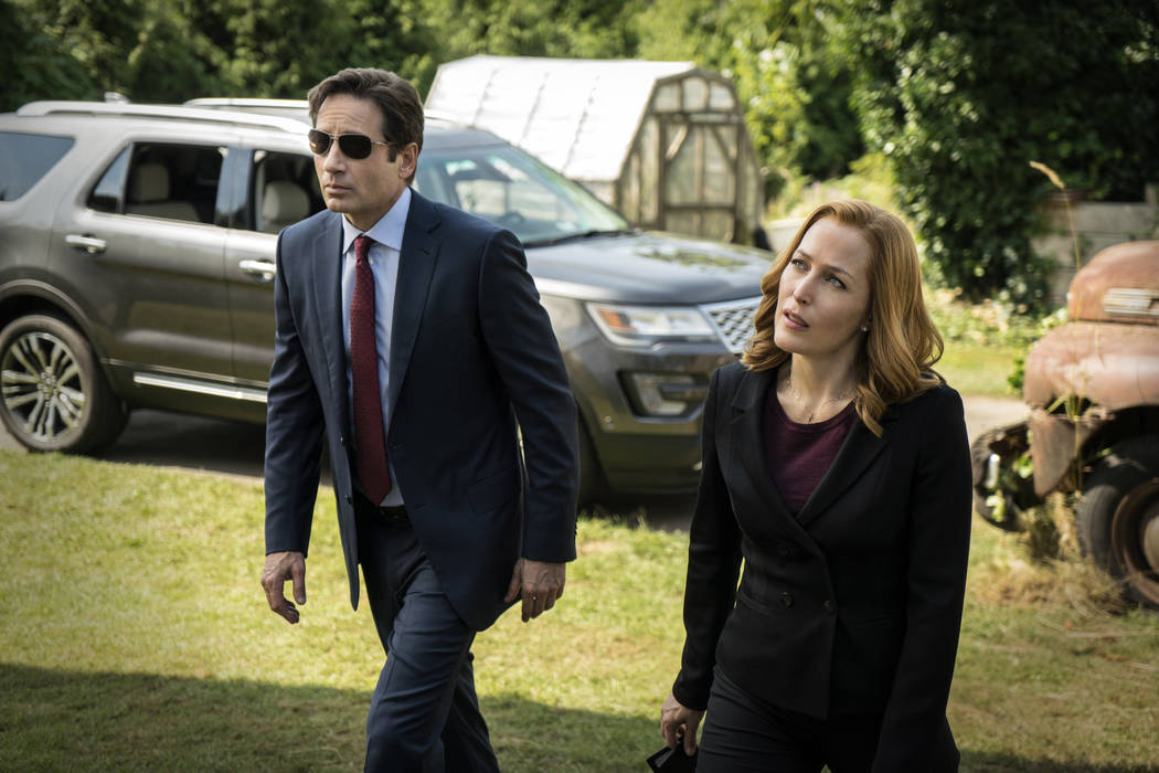 "This photo provided by FOX shows, David Duchovny, left, as Fox Mulder and Gillian Anderson as Dana Scully in an episode of ""The X-Files."" Fox said Thursday it has ordered a secon ..."