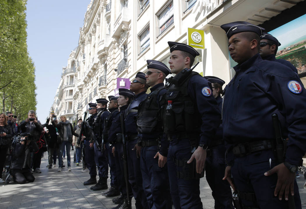 A dozen of police officers stand at attention at the place where a police officer was killed Thursday on the Champs-Elysees boulevard, Friday, April 21, 2017 in Paris. Christophe Ena AP