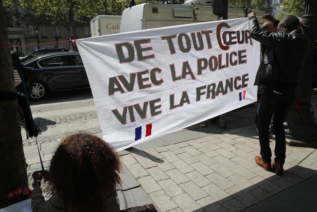 "Three people set up a banner reading ""Our hearts with the police, Long live France"" at the place where a police officer was killed Thursday on the Champs-Elysees boulevard, Friday, April 21, 2017  ..."