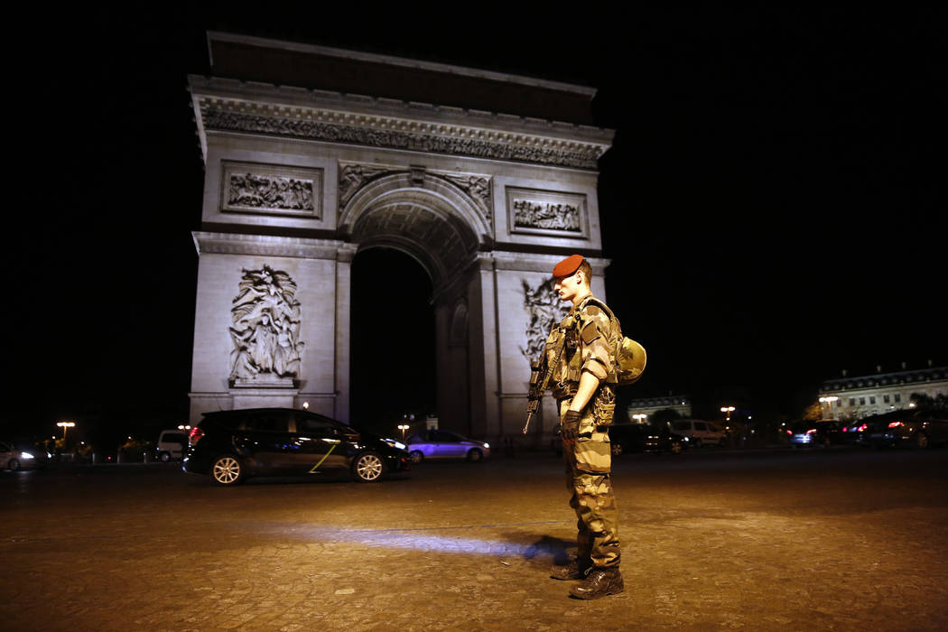 A soldier stands guard near the Arc of Thriomphe at the top of the Champs-Elysees in Paris after a fatal shooting in which a police officer was killed along with an attacker, Thursday, April 20, 2 ...