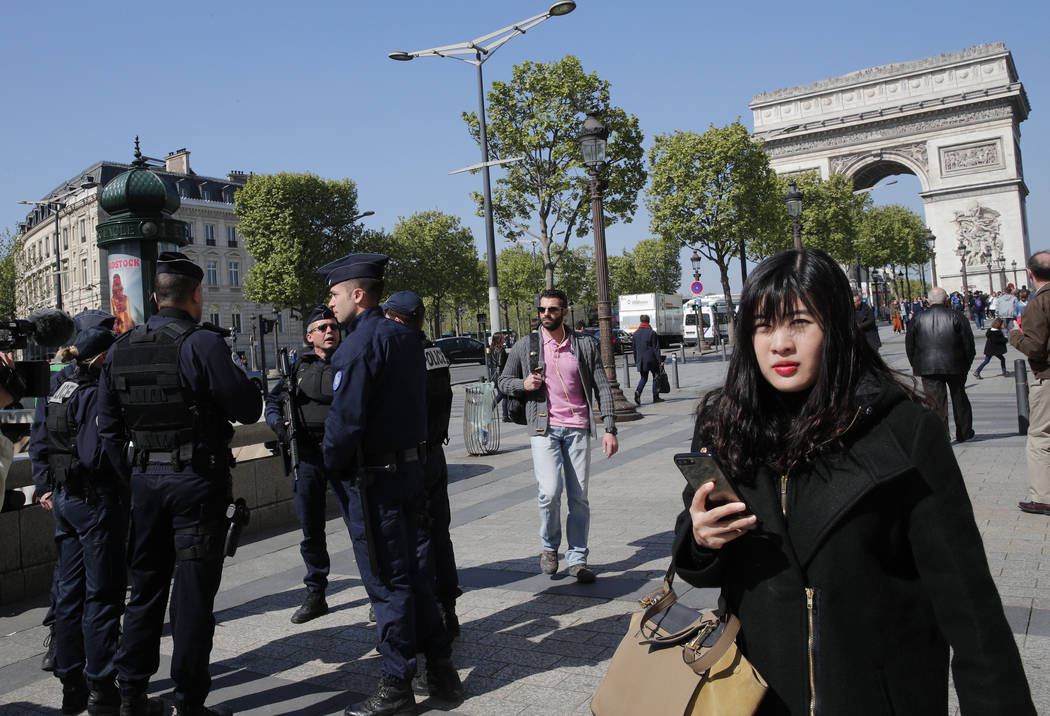 French police officers patrol on the Champs-Elysees with the Arc de Triomphe in background, in Paris, April 21, 2017. France began picking itself up Friday from another deadly shooting claimed by  ...