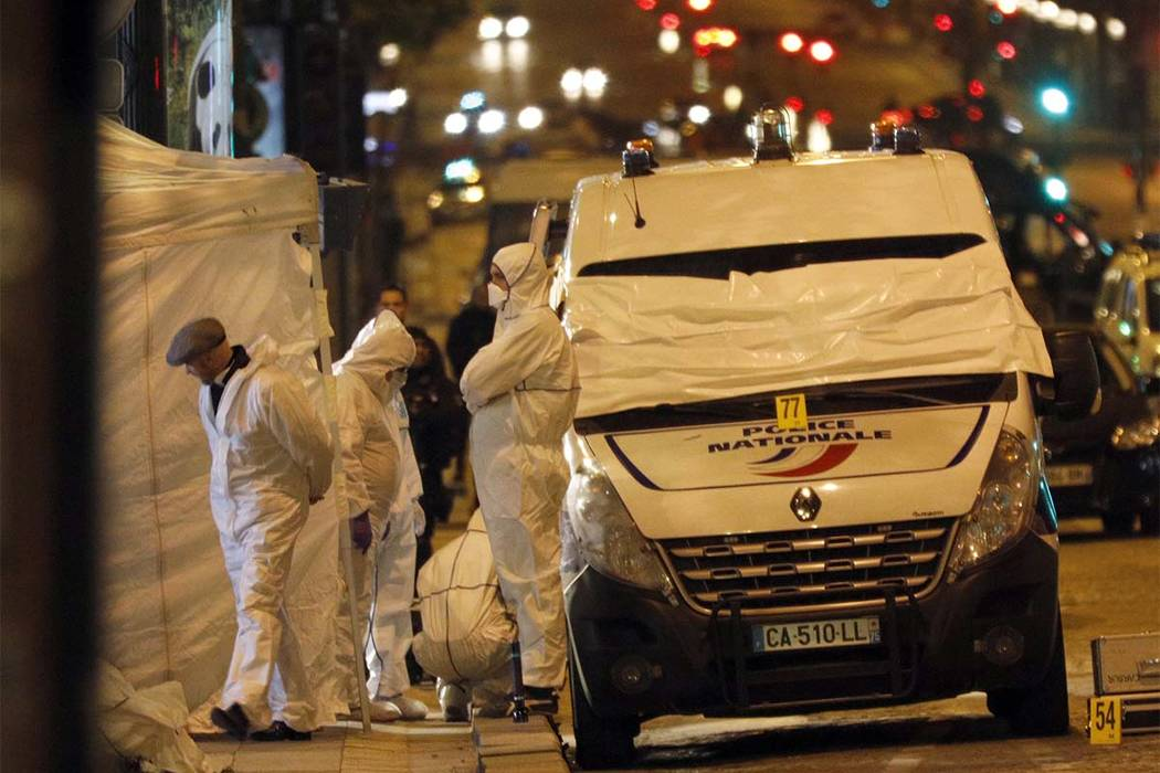 Forensic experts investigate the crime scene after a fatal shooting in which a police officer was killed along with an attacker on the Champs Elysees avenue in Paris, France, Friday, April 21, 201 ...