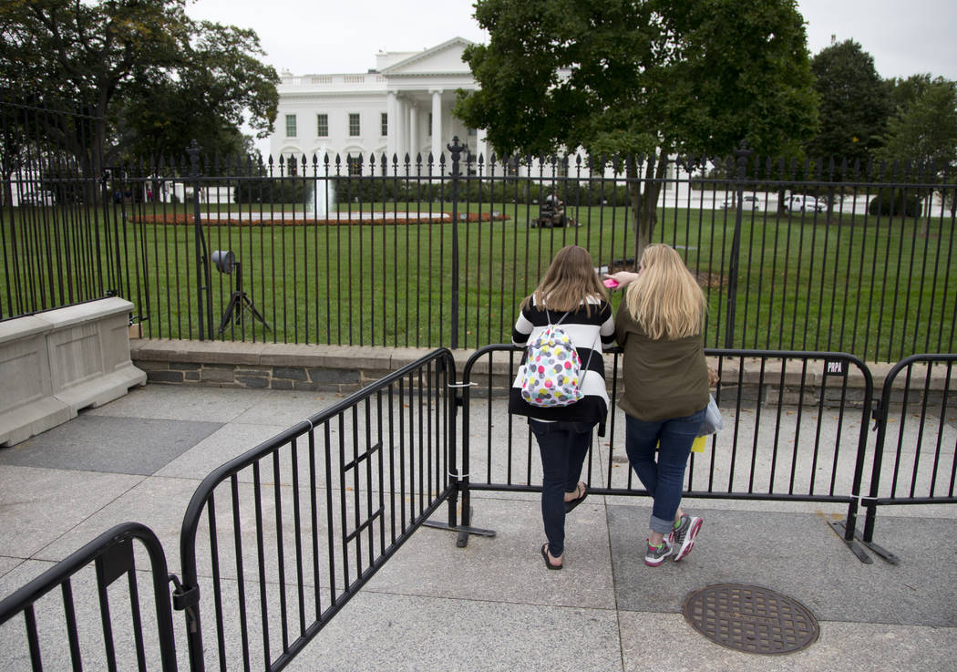 FILE - In this Oct. 3, 2014 file photo, two women lean against a temporary barrier along Pennsylvania Avenue in front of the White House in Washington. The U.S. Secret Service says it is restricti ...