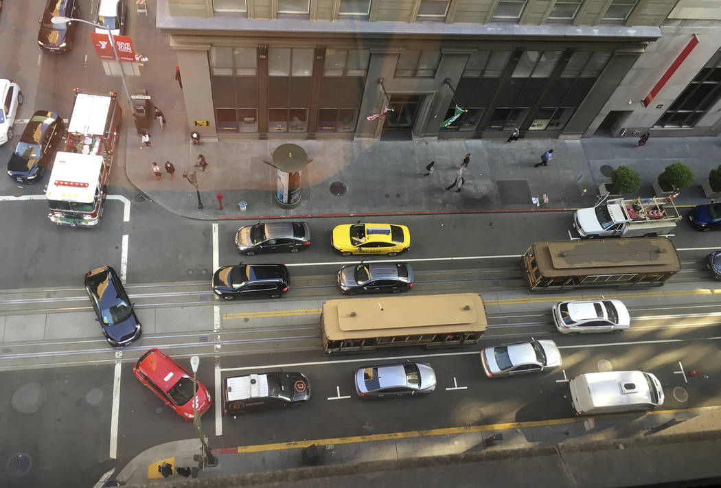 A fire truck at top left and other traffic try to make their way around a pair of idled cablecars on California Street after a large power outage Friday, April 21, 2017, in San Francisco. Eric Ris ...