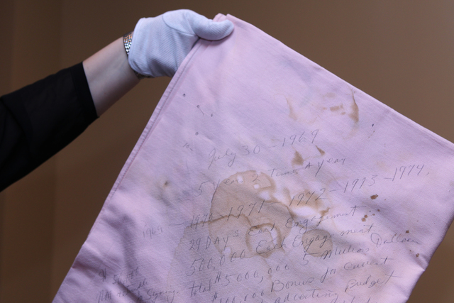 Angie Marchese, director of archives at Elvis Presley Enterprises, shows a table cloth Elvis Presley used to negotiate his contract extension with Las Vegas Hilton that was part of the Direct from ...