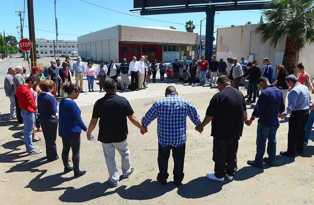 Pastors and church leaders gather for a final prayer following a prayer walk for the victims of Tuesday's triple-homicide near downtown Fresno, Calif., Thursday, April 20, 2017. Members of the Pas ...