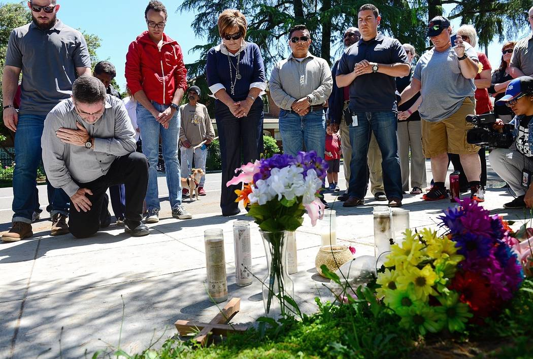 Pastor Tim Rolen, left, of New Hope Community Church in Clovis, kneels to pray with other church leaders at the site where Mark Gassett was shot and killed in Tuesday's triple-homicide, during a p ...
