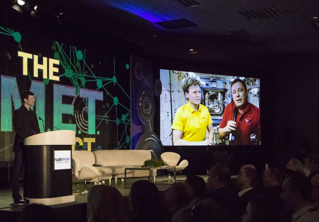 AWS Elemental CEO Sam Blackman, left, listens to a 4k livestream showing NASA astronauts Peggy Whitson, left, and Jack Fischer, both aboard the International Space Station, at the National Associa ...