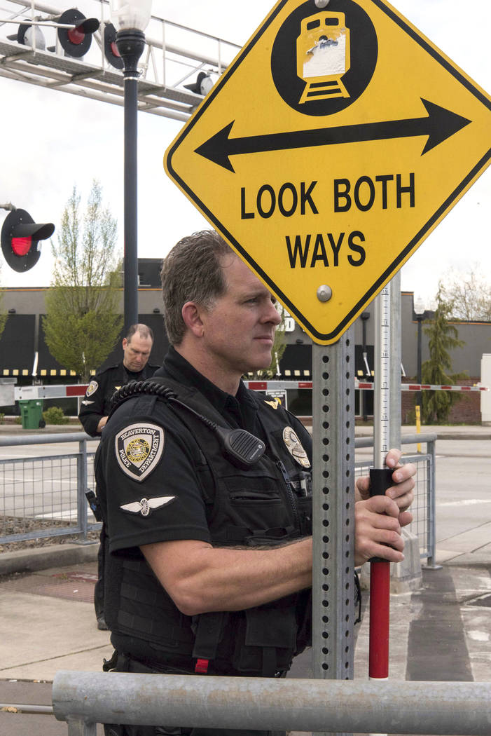 Police survey the scene at a railroad crossing where a woman was struck by a locomotive in Beaverton, Ore., Thursday, April 20, 2017. An Oregon woman who was distracted by her cellphone is hospita ...