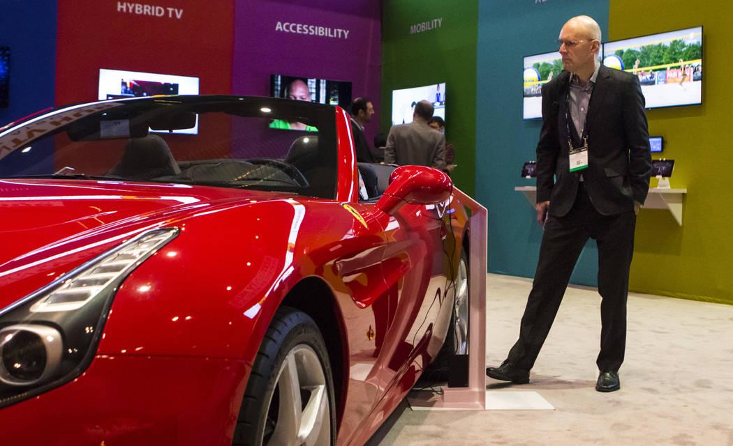 Yarko Krupa checks out a 2016 red Ferrari at the National Association of Broadcasters Show in Las Vegas on Wednesday, April 26, 2017. Miranda Alam Las Vegas Review-Journal @miranda_alam