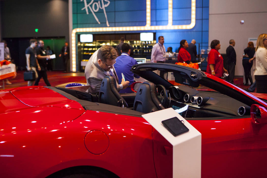 Carlos Andre checks out a 2016 red Ferrari at the National Association of Broadcasters Show in Las Vegas on Wednesday, April 26, 2017. Miranda Alam Las Vegas Review-Journal @miranda_alam