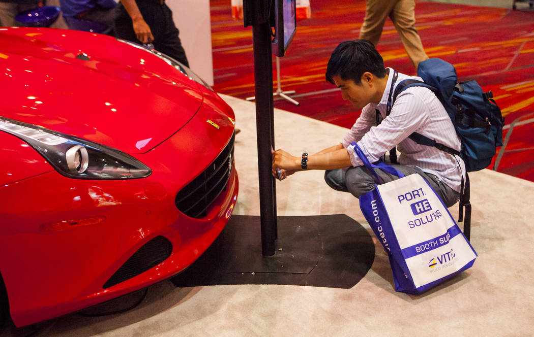 Anderson Tsai takes a picture of the grill on a 2016 red Ferrari at the National Association of Broadcasters Show in Las Vegas on Wednesday, April 26, 2017. Miranda Alam Las Vegas Review-Journal @ ...