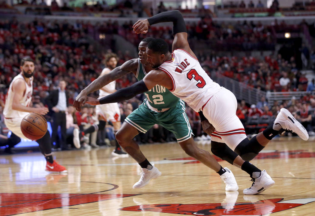 Chicago Bulls' Dwyane Wade (3) and Boston Celtics' Terry Rozier battle for a loose ball during the first quarter of Game 3 of a first-round NBA playoff basketball series in Chicago, Friday, April  ...