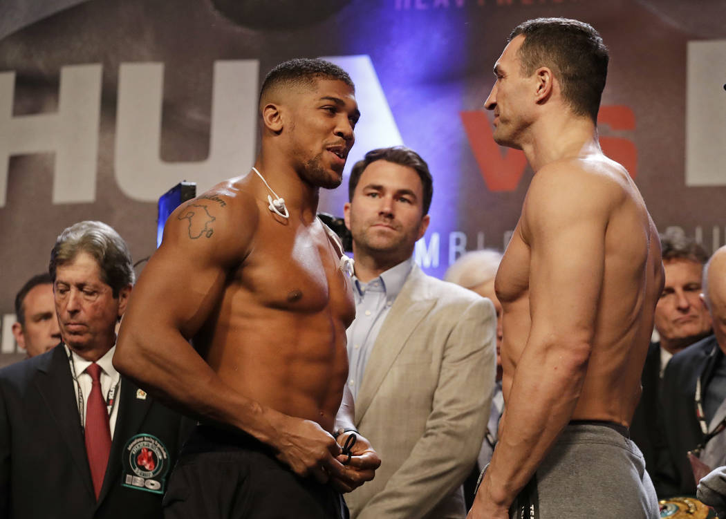 British boxer Anthony Joshua, left, and Ukrainian boxer Wladimir Klitschko take part in their weigh-in at Wembley Arena in London, Friday, April 28, 2017. They are due to fight for Joshua's IBF an ...
