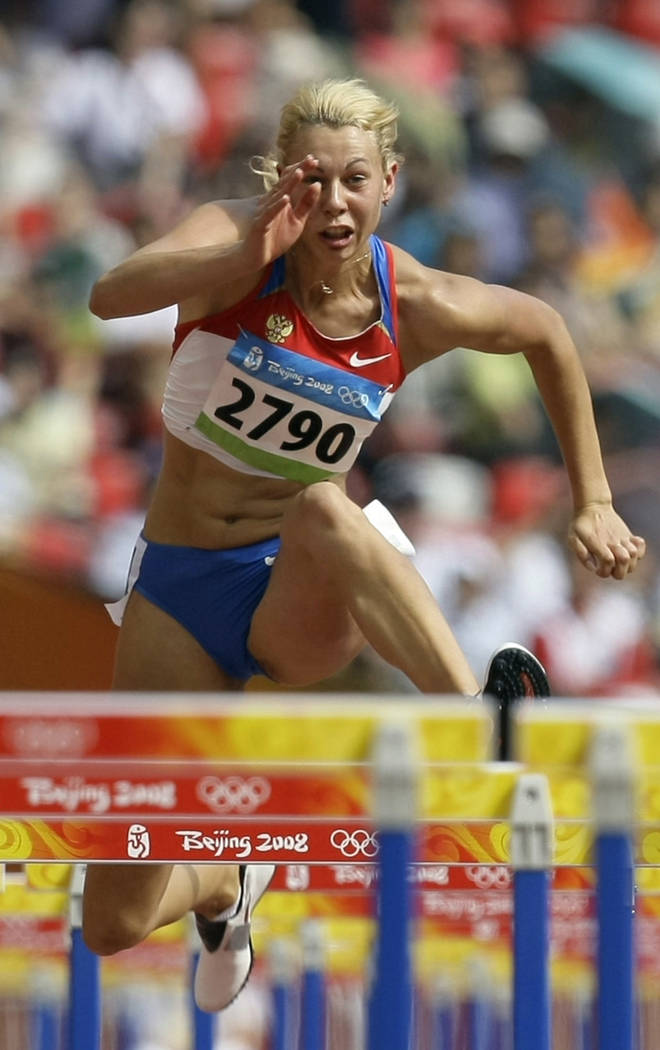 In this Aug. 15, 2008 file photo Russia's Tatiana Chernova clears a hurdle in the heptathlon during the athletics competitions in the National Stadium at the Beijing 2008 Olympics in Beijing. IOC  ...