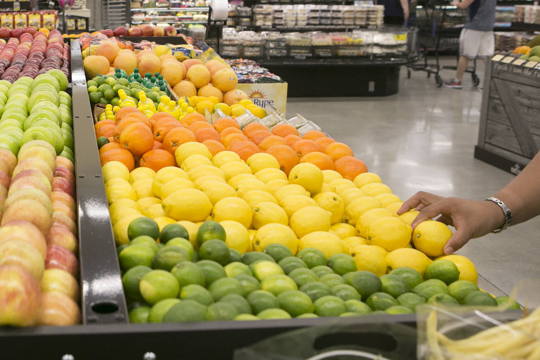 A customer grabs a lemon while browsing through produce during the grand opening of Albertsons on Blue Diamond Road on Wednesday, April 26, 2017, in Las Vegas. Bridget Bennett  Las Vegas Review-Jo ...
