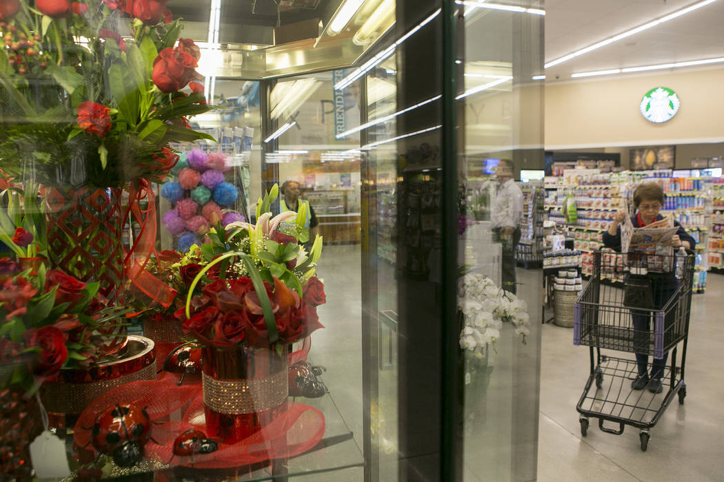 Flowers are set on display while a customer pages through an advertisement during the grand opening of Albertsons on Blue Diamond Road on Wednesday, April 26, 2017, in Las Vegas.Bridget Bennett  L ...