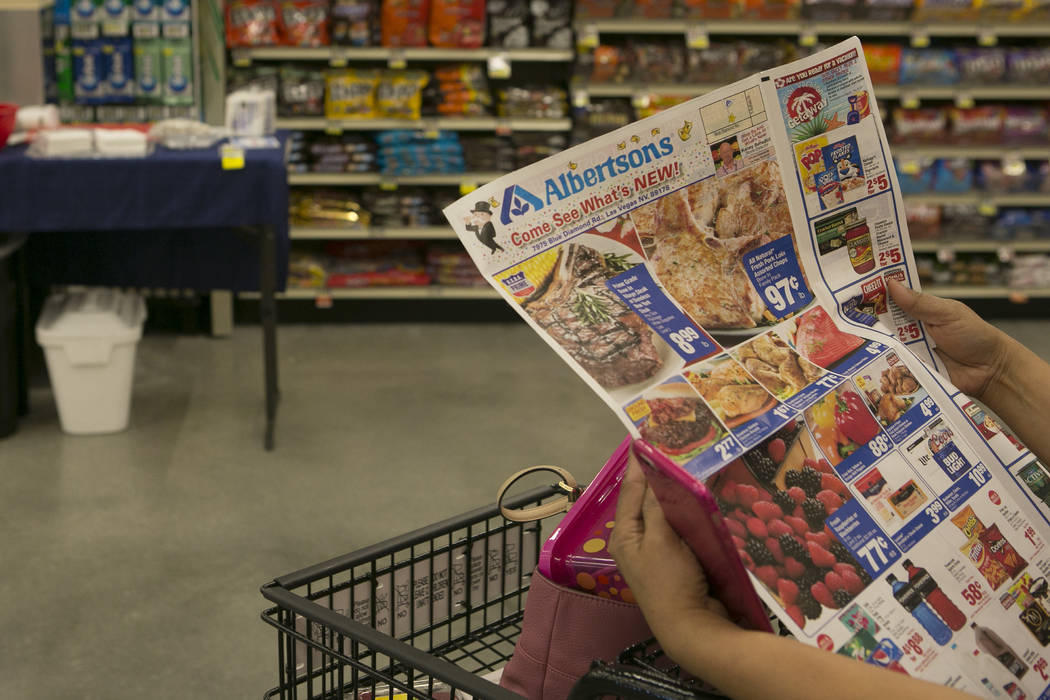 A customer pages through an advertisement during the grand opening of Albertsons on Blue Diamond Road on Wednesday, April 26, 2017, in Las Vegas.Bridget Bennett  Las Vegas Review-Journal @bridgetk ...