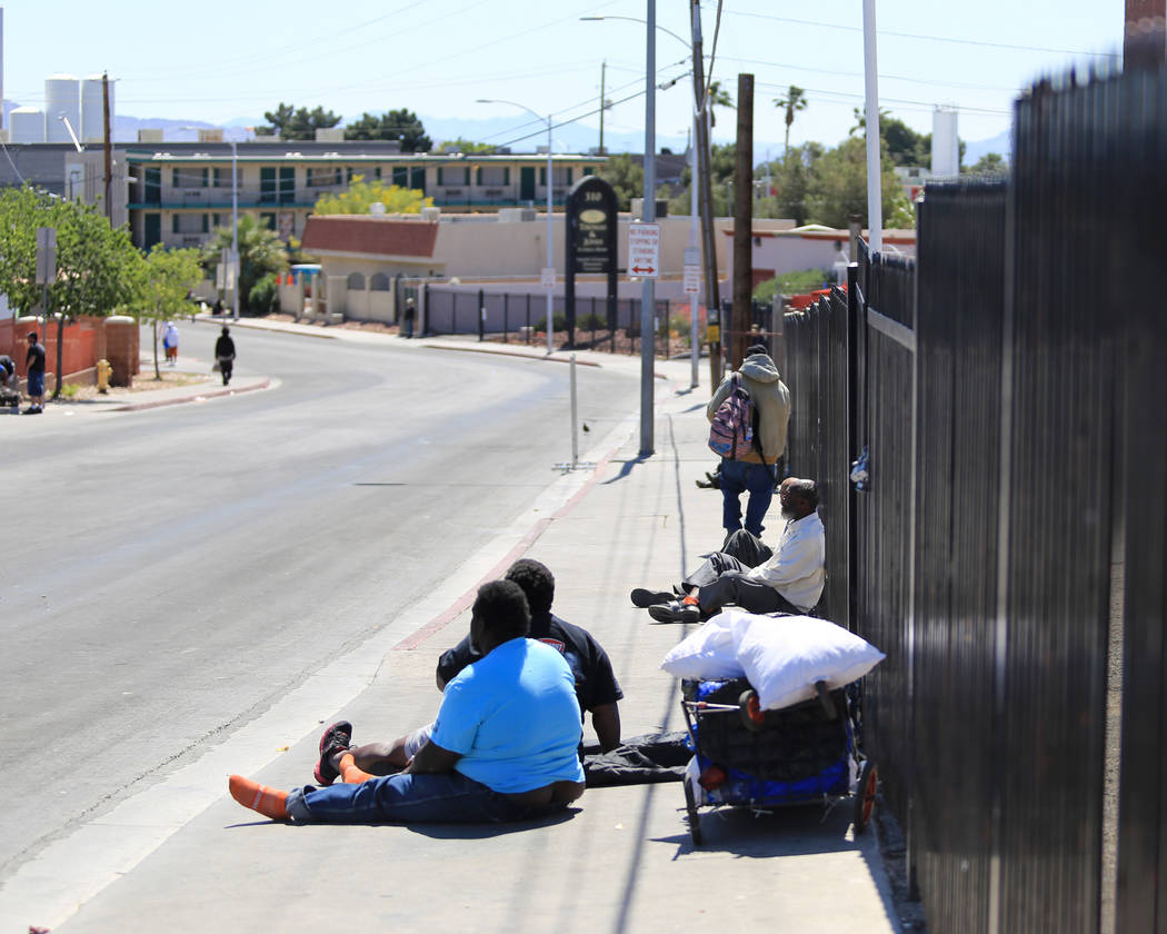 People sit on Foremaster Lane in Las Vegas, on Friday, April 28, 2017, in front of land that the city of Las Vegas wants to turn into a campus that will bring homeless providers together and give  ...