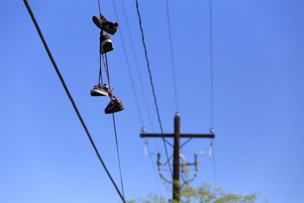 Shoes hang from a power line on Main Street at Foremaster Lane in Las Vegas, on Friday, April 28, 2017, in front of land that the city of Las Vegas wants to turn into a campus that will bring home ...