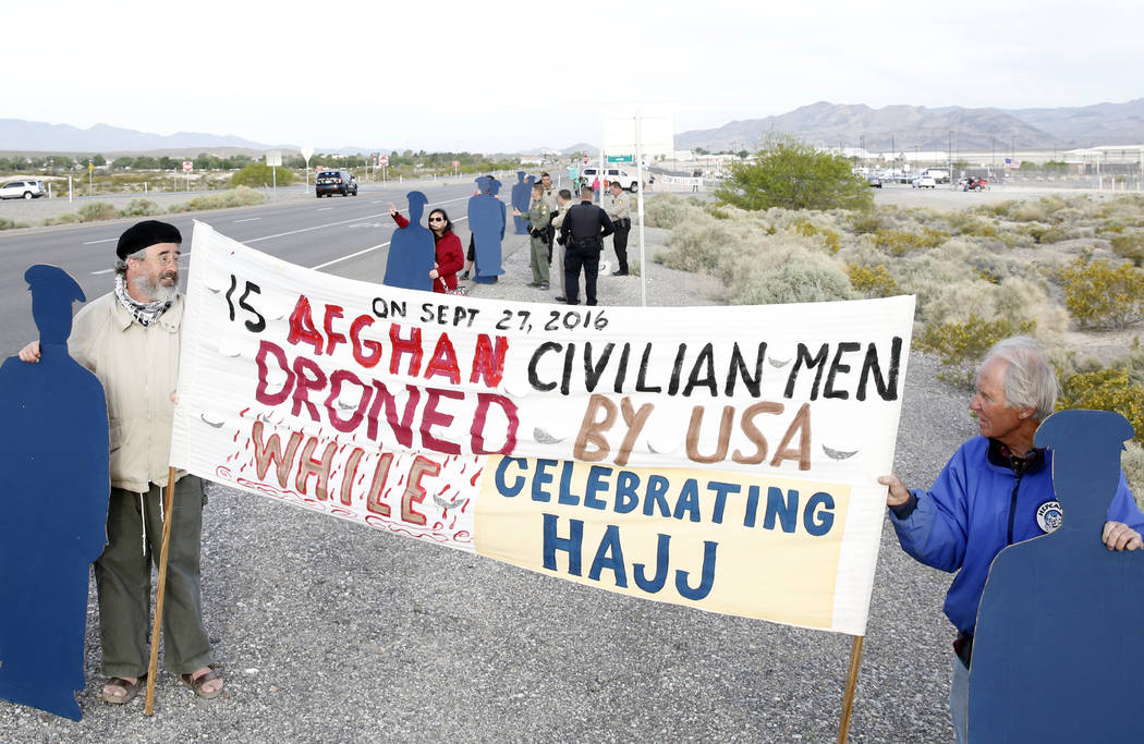 Anti-drone warfare protesters, Brian Terrell, left, and Dennis DuVall hold life-size cardboard human figures outside Creech Air Force Base at Indian Springs on Monday, April 24, 2017, to honor the ...