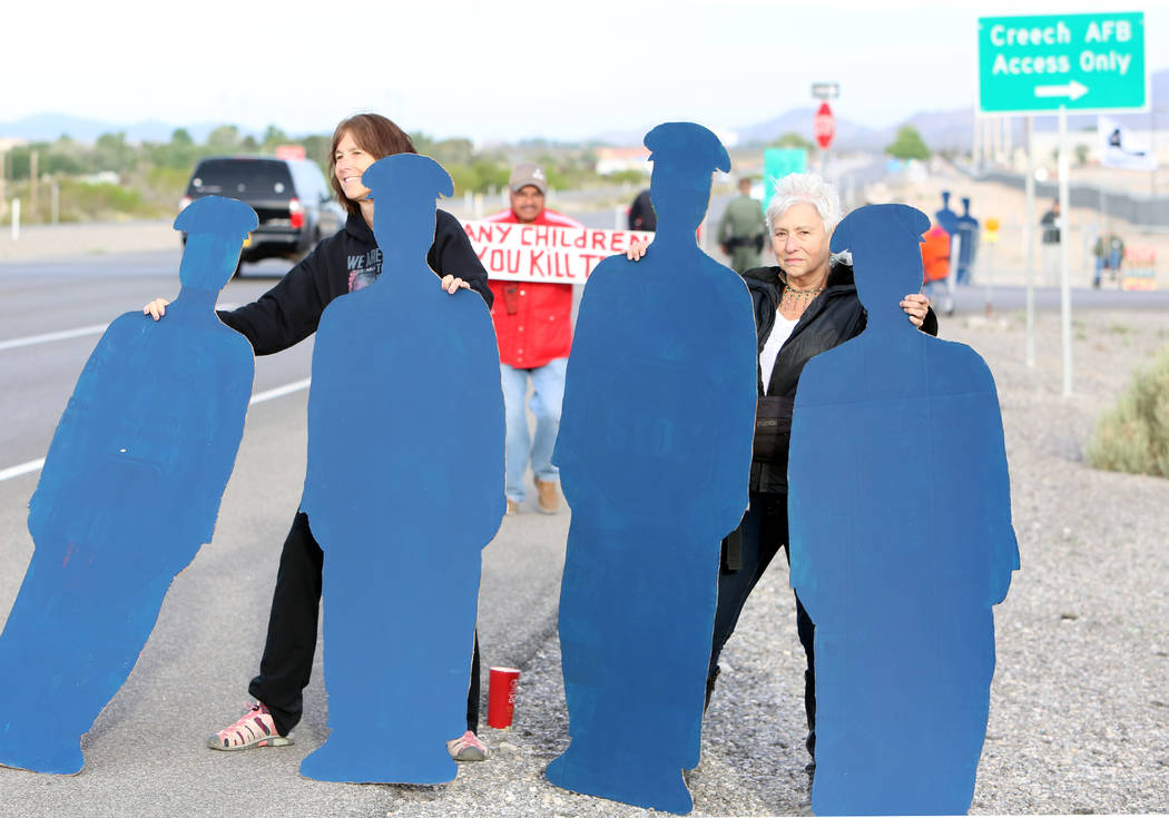 Anti-drone warfare protesters Laurie Tanner, left, and GG Winter hold life-size cardboard human figures outside Creech Air Force Base at Indian Springs on Monday, April 24, 2017, to honor the 15 c ...