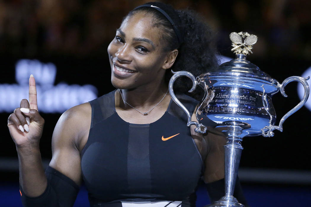 In this Jan. 28, 2017, file photo, Serena Williams holds up a finger and her trophy after defeating her sister, Venus, in the women's singles final at the Australian Open tennis championships in M ...
