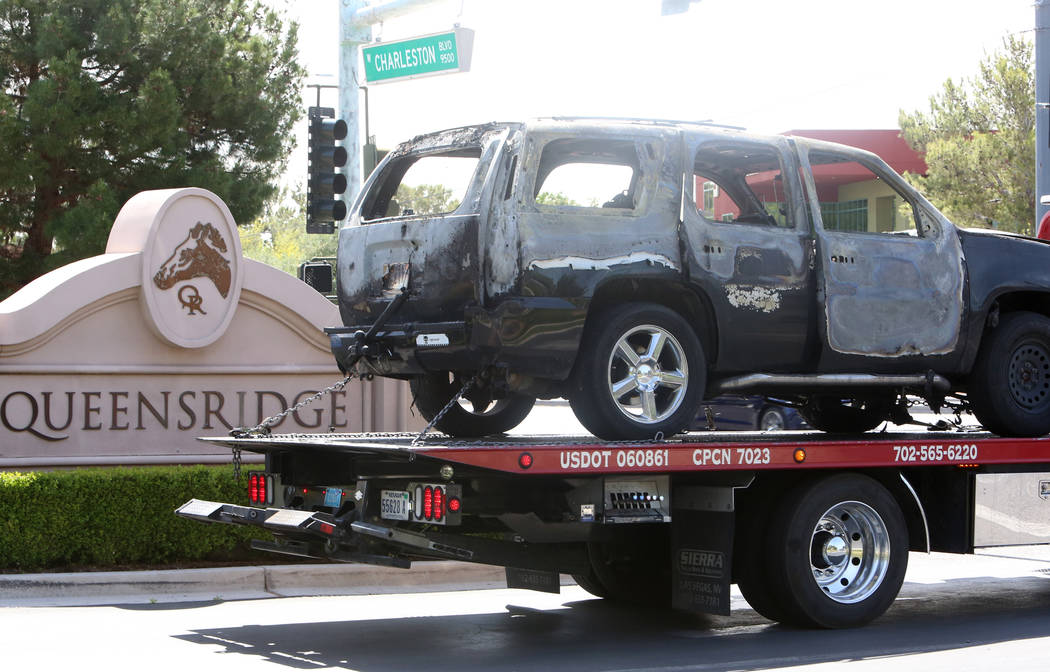 A burned vehicle is towed away from the Queensridge gated community where police say a man drove his vehicle into the entrance gate, then drove to a residence and lit the truck on fire, Wednesday, ...