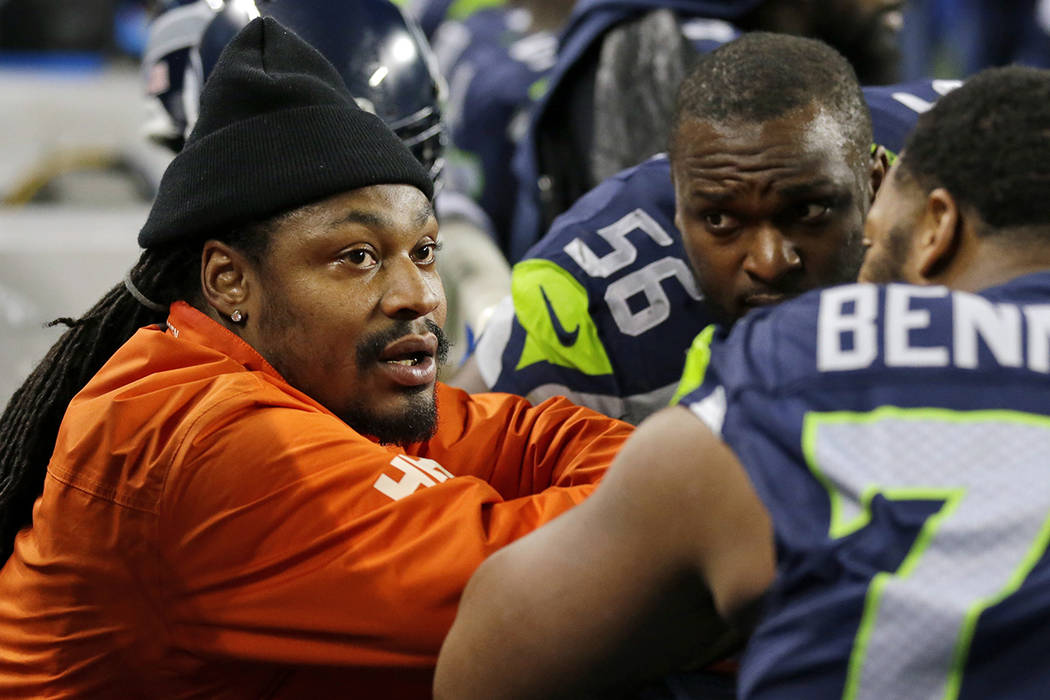 In this Dec. 4, 2016, file photo running back Marshawn Lynch, left, chats on the sidelines players on the bench in the second half of an NFL football game against the Carolina Panthers in Seattle. ...