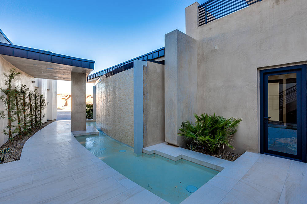 Walking up the main entrance, a 400-square-foot long cascading waterfall feature provides a sense of tranquility. (Growth Luxury Homes)