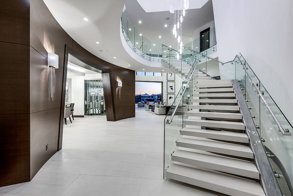 The colossal 7-foot-by-foot pivot door welcomes a grand foyer and stunning glass staircase. (Growth Luxury Homes)