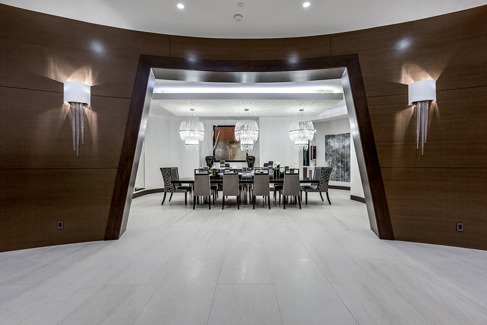 Off the foyer, a luxurious dining room is highlighted by three custom-designed crystal chandeliers. (Growth Luxury Homes)