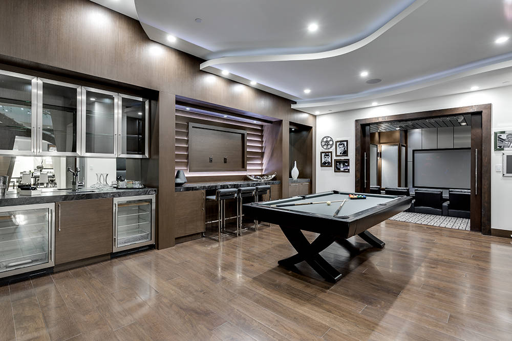 Walnut flooring accent the game room off the main living area. (Growth Luxury Homes)