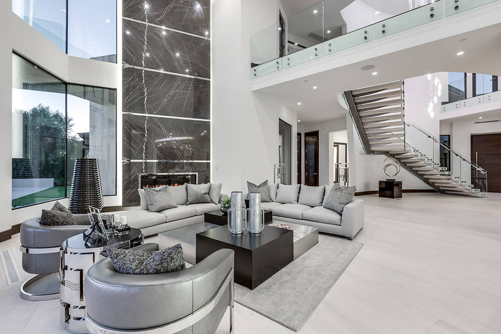 Limestone floors imported from Portugal line the main level living space and stairwell. (Growth Luxury Homes)