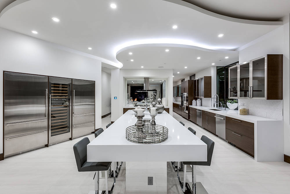 The contemporary kitchen offers functionality as well as a sleek livable feel with Pentax white quartz countertops and walnut cabinetry. (Growth Luxury Homes)