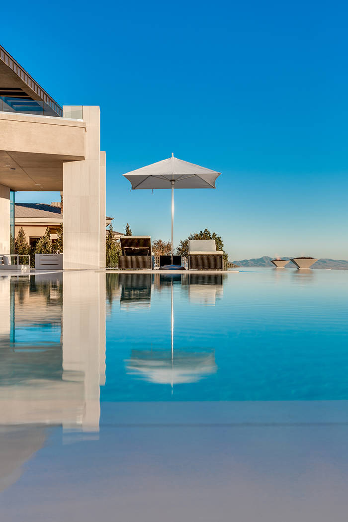 The pool has fire features and a resort feel. (Growth Luxury Homes)