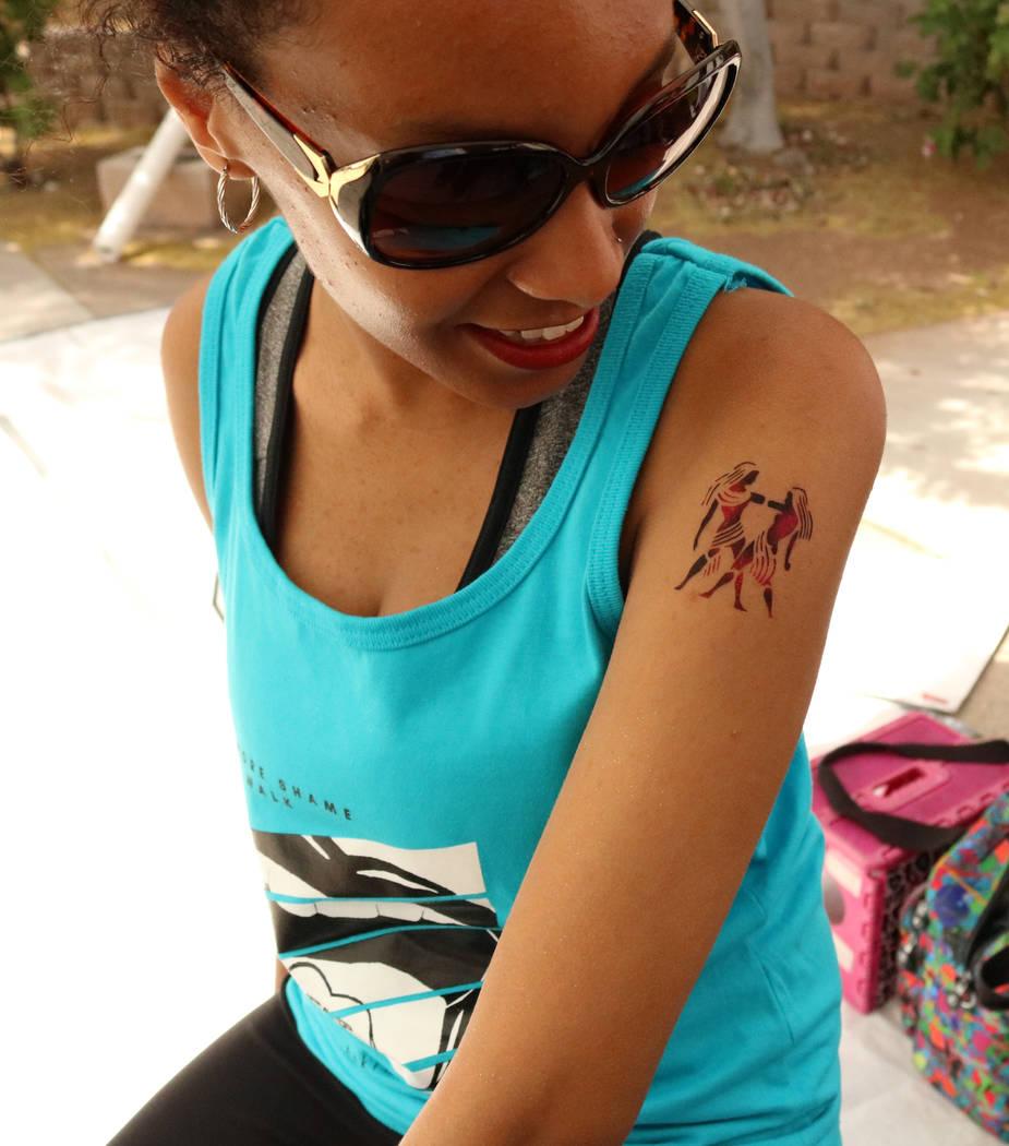 "UNLV junior Eden Alem admires her temporary tattoo before ""No More Shame Slut Walk"" at the UNLV campus, Wednesday, April 26, 2017. Gabriella Benavidez Las Vegas Review-Journal @g ..."