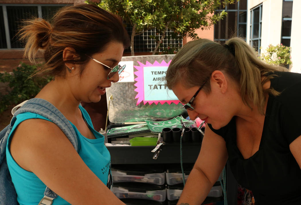 """UNLV senior Alexa Matoes, left, discusses her temporary tattoo with artist Lucy Veltri before """"No More Shame Slut Walk"""" at the UNLV campus, Wednesday, April 26, 2017. Gabriella B ..."""