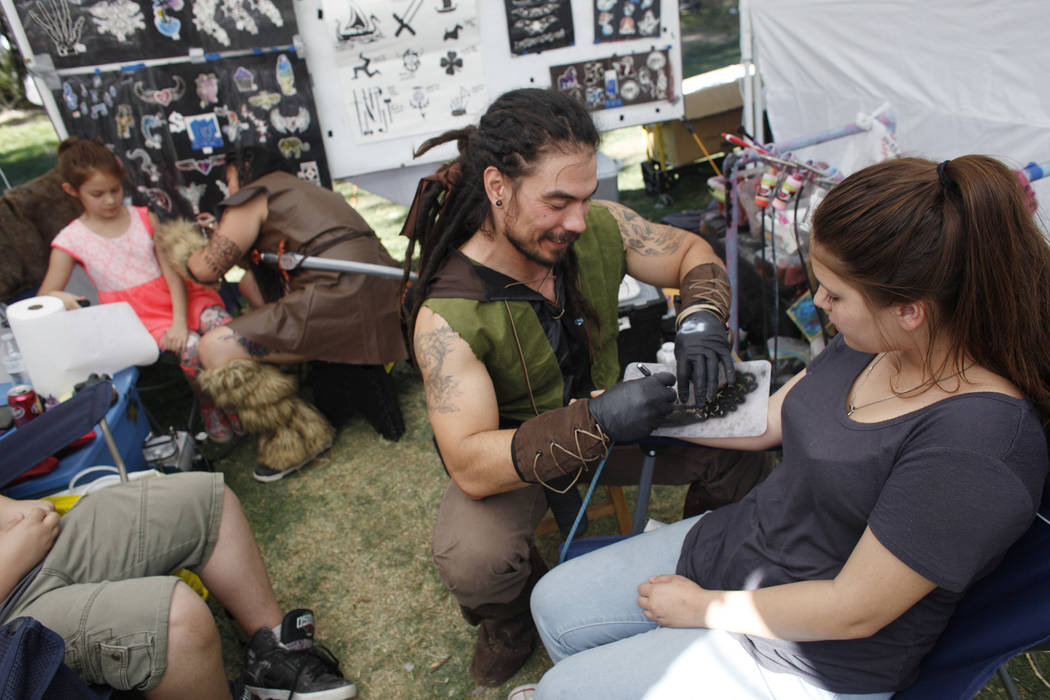 Tyrone Landry paints a temporary tattoo on Trinity Rosales, 15, at the Las Vegas Highland Games on Sunday, April 30, 2017, at Floyd Lamb Park in Las Vegas. Rachel Aston Las Vegas Review-Journal @r ...