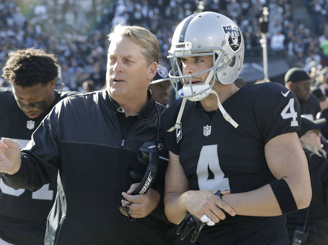 Oakland Raiders head coach Jack Del Rio, left, talks with quarterback Derek Carr (4) before an NFL football game against the Indianapolis Colts in Oakland, Calif., Saturday, Dec. 24, 2016. (AP Pho ...