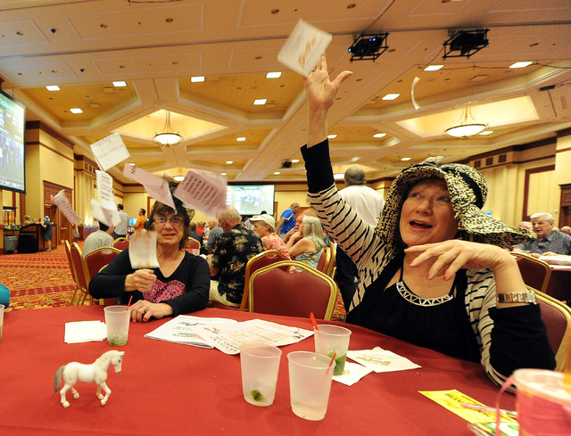 Marge Raglo, left, and Teresa VanAcker, both members of the Desert Newcomers Club, throw their non-winning tickets up in the air in disgust during a viewing party for the Kentucky Derby horse race ...