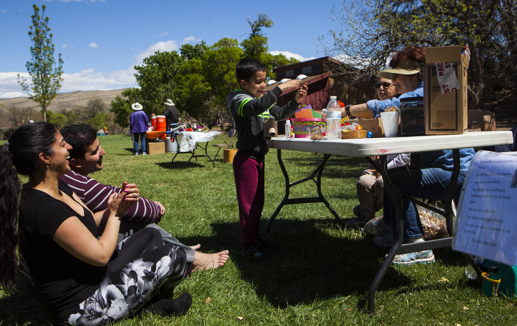 Lio Bayon Jr., 4, plays a memory match game with volunteers Marisol Drank, left and Lois Bloom as his parents Arianna Gonzalez, left, and Lio Bayon watch during the Mojave Spring Fling Festival at ...