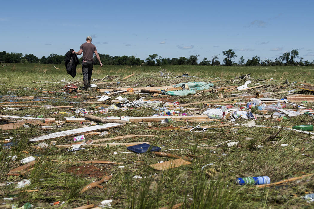 Kyle Allen walks his parents' property in Canton, Texas on Sunday, April 30, 2017, looking for personal items. Severe storms including tornadoes swept through several small towns in East Texas, ki ...