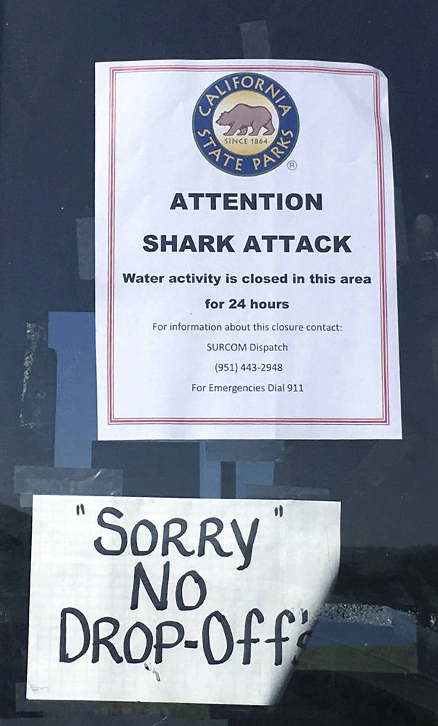 In this Sunday, April 30, 2017 photo, a sign warns beach goers at San Onofre State Beach after a woman was attacked by a shark in the area Saturday, along the Camp Pendleton Marine base in San Die ...