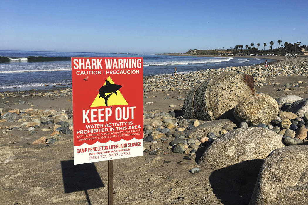 A sign warns beach goers April 30, 2017, at San Onofre State Beach after a woman was attacked by a shark in the area Saturday along the Camp Pendleton Marine base in San Diego County, California.  ...