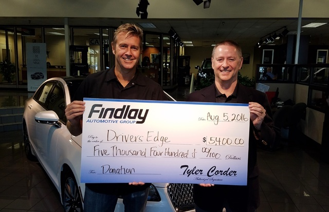 COURTESY Findlay Automotive Group CFO Tyler Corder, right, presents a donation to Driver's Edge founder Jeff Payne.