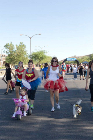 Two and four-legged Candlelighters supporters walk through the Mountain's Edge community. The Superhero 5K with Chet Buchannan is Saturday, Sept. 10, at the master plan's Exploration Park. (Co ...